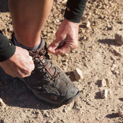 A female hiker lacing up her boots