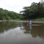 Walkers wading through a river on Fiji