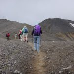 Hikers on a narrow path against grey Icelandic skies