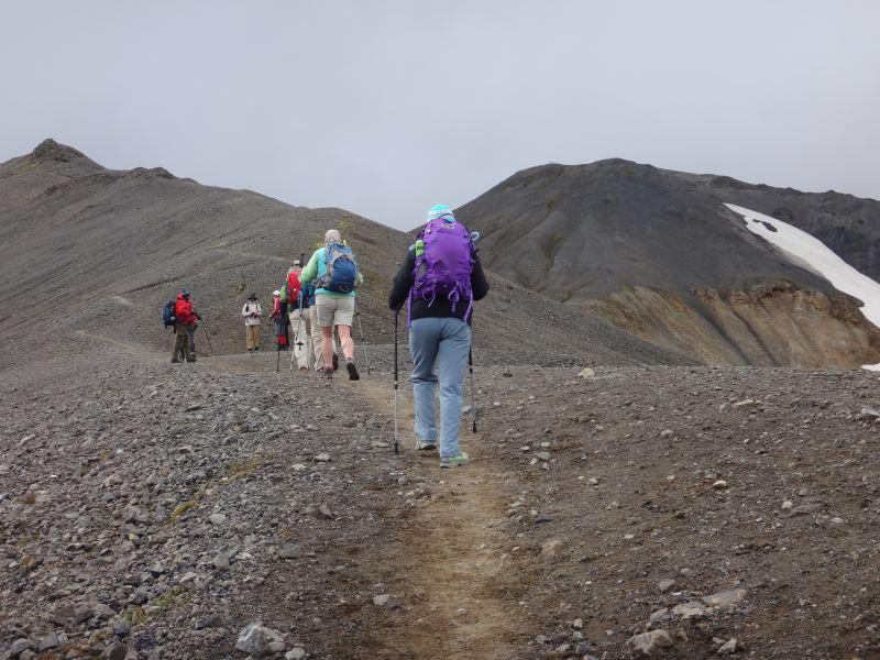 Hikers on a narrow path against grey Icelandic skies